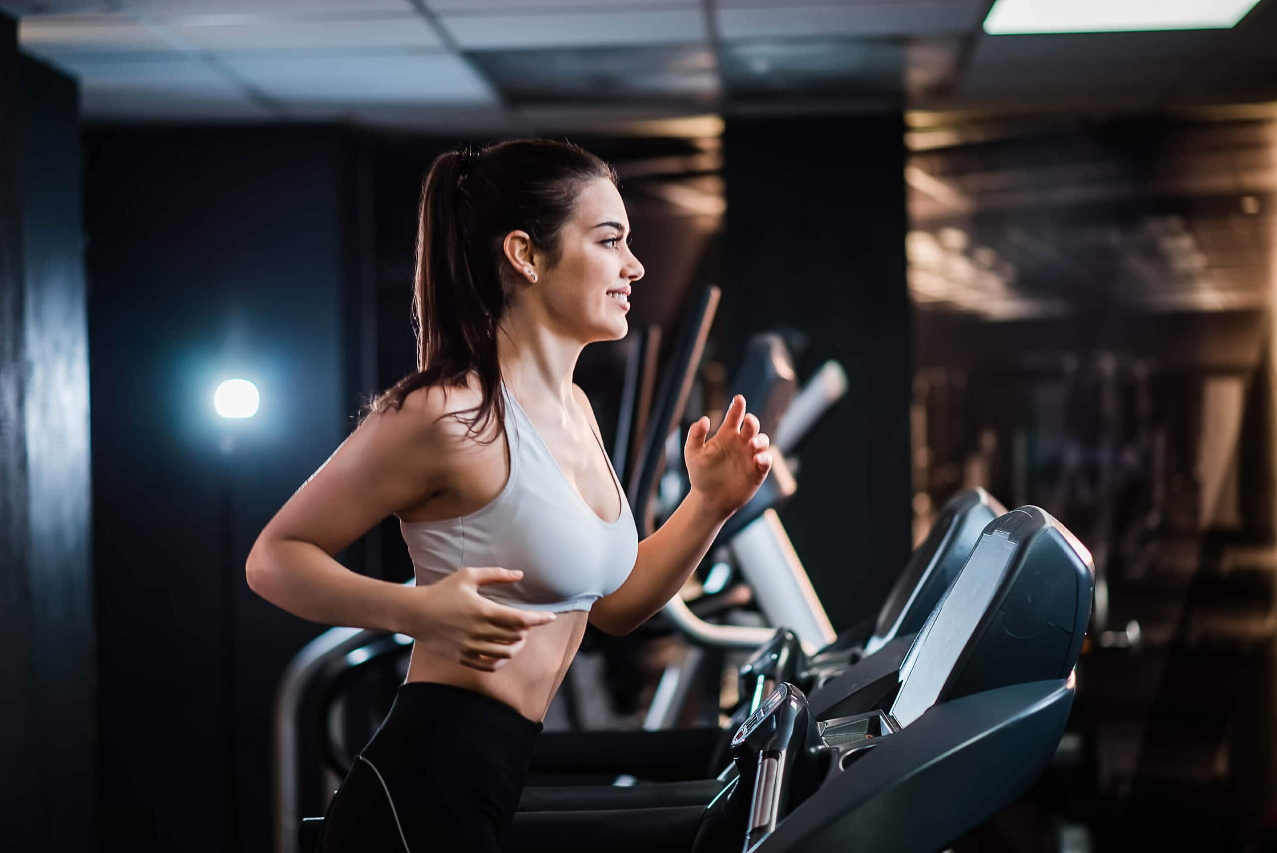 young-sports-woman-with-ponytail-working-out-gym-running-treadmill-side-view (1)
