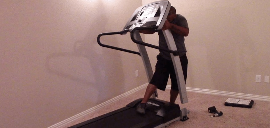 Person Setting Up a Treadmill in the Garage